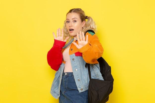 Młoda Studentka W Nowoczesne Ubrania Pozowanie Z Ostrożnością Na żółto Darmowe Zdjęcia