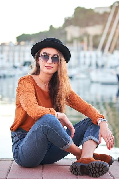 Młoda stylowa dziewczyna w porcie morskim Premium Zdjęcia