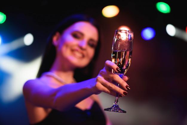 Młoda świętuje kobieta czarna sukienka, trzymając kieliszek szampana. przyjęcie. Premium Zdjęcia