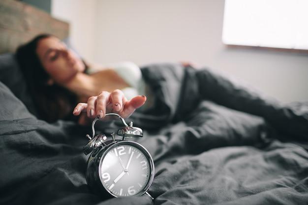 Młoda Sypialna Kobieta I Budzik W Sypialni W Domu. Dziewczyna Zaspała W łóżku I Zszokowała Budzika Premium Zdjęcia