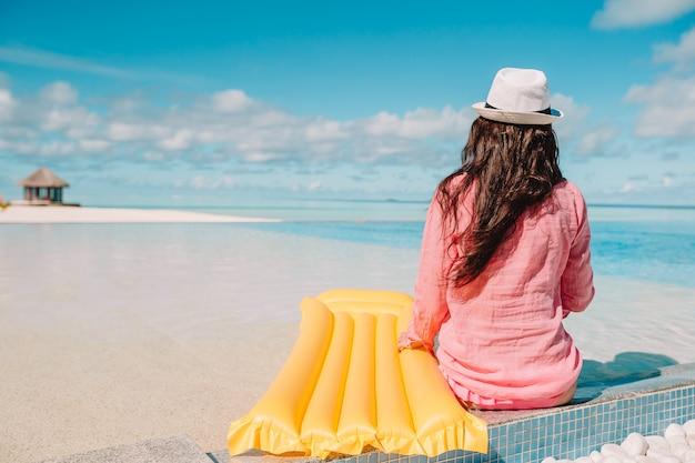 Młoda szczęśliwa kobieta relaksuje w pływackim basenie Premium Zdjęcia