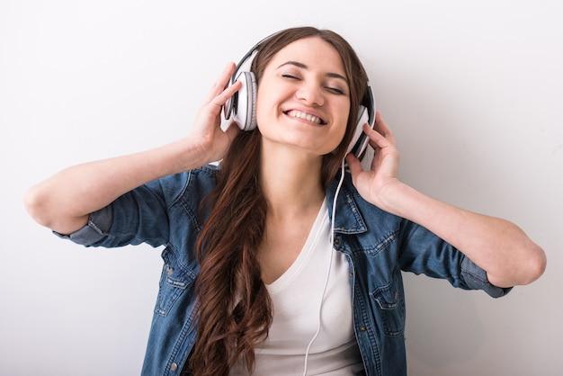 Młoda szczęśliwa kobieta słucha muzyka z hełmofonem. Premium Zdjęcia