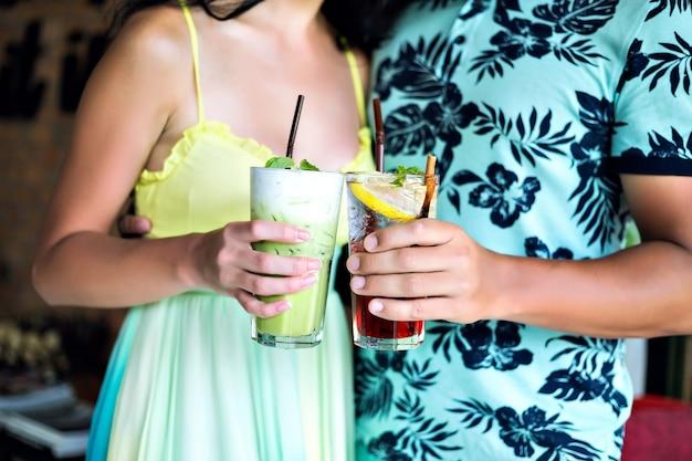 Młoda Szczęśliwa Para Pije Smaczne Słodkie Koktajle W Tropikalnym Barze, Uśmiecha Się I Dobrze Się Bawi, Jasne Ubrania I Pozytywne Emocje. Darmowe Zdjęcia