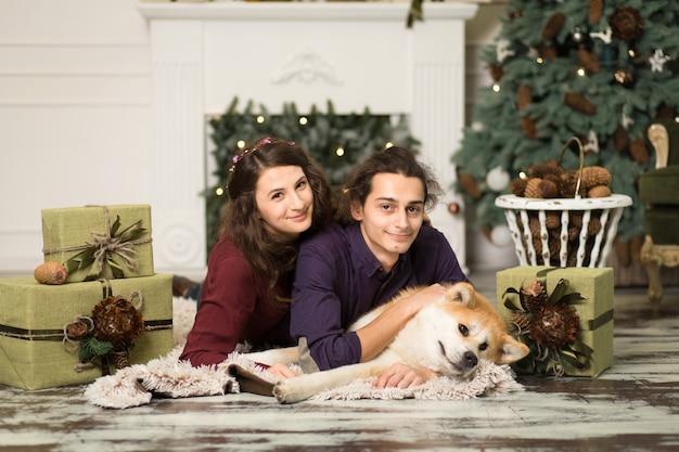 Młoda szczęśliwa para przytulanie uroczego psa akita inu na podłodze na święta bożego narodzenia w domu. Premium Zdjęcia