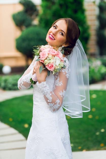 Młoda Szczęśliwa Piękna Panna Młoda W Białej Eleganckiej Sukni ślubnej Z Bukietem Pozowanie Na świeżym Powietrzu W Parku. Darmowe Zdjęcia