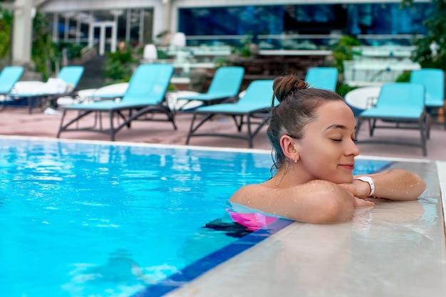 Młoda Szczęśliwa Radosna Kobieta Z Zamkniętymi Oczami, Korzystających Z Kąpieli W Basenie Podczas Relaksu W Ośrodku Spa Wellness Premium Zdjęcia