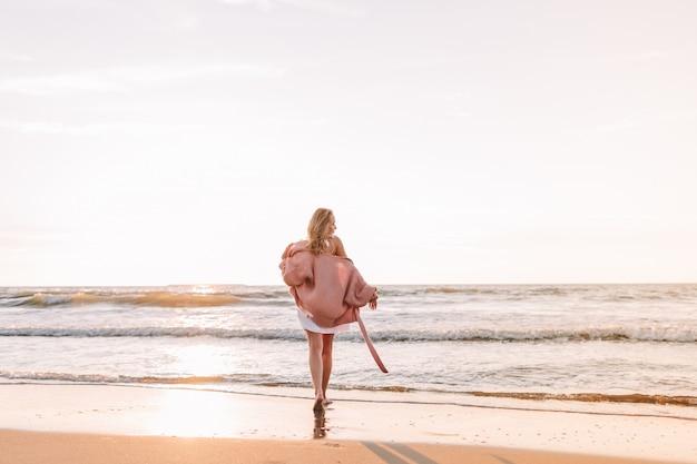 Młoda Szczupła Kobieta Stoi Samotnie Na Plaży Lub Oceanie I Patrzy W Horyzont. Kobieta Ubrana W Ciepły Sweter. Stonowanych Premium Zdjęcia