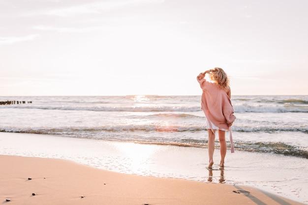 Młoda Szczupła Kobieta Stoi Samotnie Na Plaży Lub Oceanie I Patrzy W Horyzont. Kobieta Ubrana W Ciepły Sweter. Premium Zdjęcia