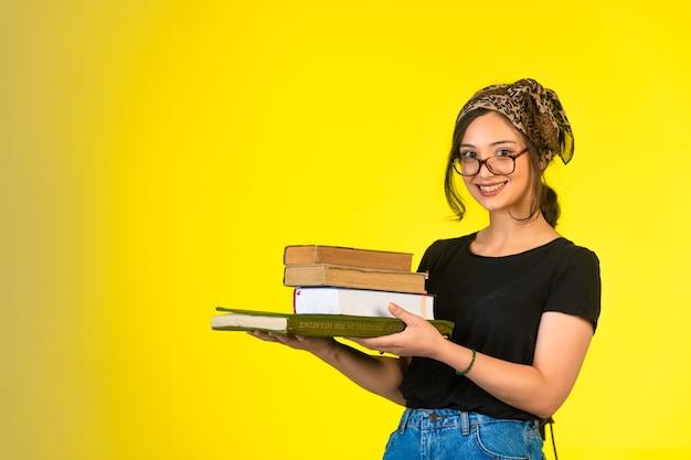Młoda Uczennica W Okularach Trzyma Jej Książki I Pozytywnie Się Uśmiecha. Darmowe Zdjęcia