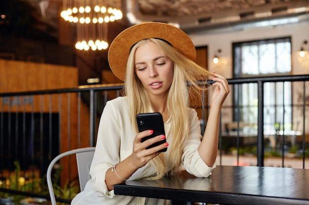 Młoda Urocza Blondynka Z Długimi Włosami Trzymając Telefon W Ręku I Patrząc Na Ekran Ze Spokojną Twarzą, Ubrana W Brązowy Kapelusz I Białą Koszulę Darmowe Zdjęcia