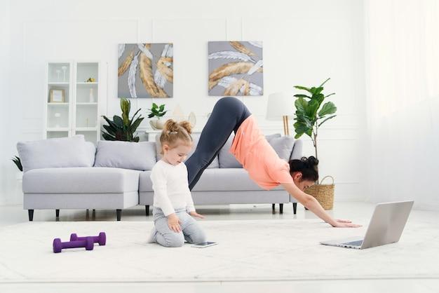 Młoda Urocza Mama Wykonuje ćwiczenia Rozciągające I ćwiczy Jogę Z Małą Dziewczynką W Domu. Zdrowie Premium Zdjęcia