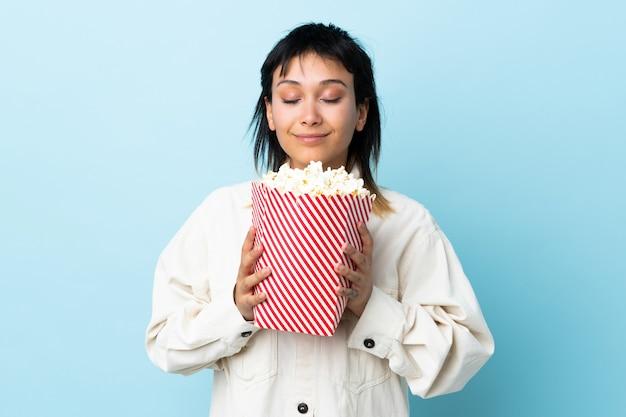 Młoda Urugwajska Kobieta Nad Błękitną ścianą Trzyma Duże Wiadro Popcorns Premium Zdjęcia