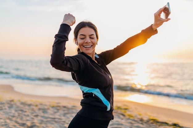 Młoda Uśmiechnięta Atrakcyjna Szczupła Kobieta Robi ćwiczenia Sportowe Na Plaży O Poranku Wschód Słońca W Strojach Sportowych, Zdrowy Styl życia, Słuchanie Muzyki Na Słuchawkach, Robienie Zdjęć Selfie Na Telefonie Wyglądającym Silnie Darmowe Zdjęcia