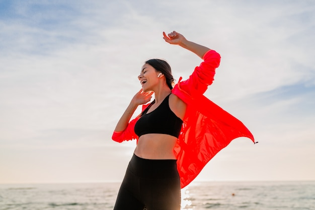 Młoda Uśmiechnięta Atrakcyjna Szczupła Kobieta Uprawia Sport O Porannym Wschodzie Słońca Tańczy Na Plaży W Stroju Sportowym, Zdrowym Stylu życia, Słuchaniu Muzyki Na Słuchawkach, Nosząc Różową Wiatrówkę, Bawiąc Się Darmowe Zdjęcia