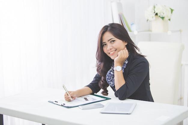 Młoda Uśmiechnięta Biznesowa Kobieta Pracuje Na Jej Papierkowej Robocie Premium Zdjęcia