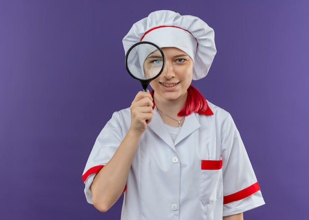 Młoda Uśmiechnięta Blondynka Kucharz Kobieta W Mundurze Szefa Kuchni Patrzy Przez Lupę Lub Lupę Na Białym Tle Na Fioletowej ścianie Darmowe Zdjęcia
