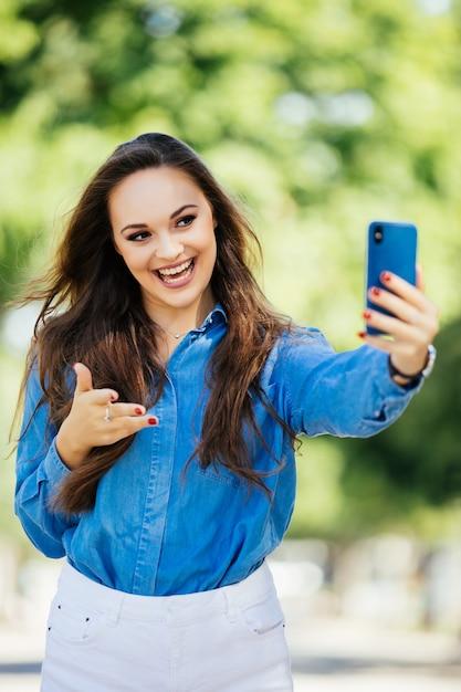 Młoda Uśmiechnięta Dziewczyna Co Selfie Macha Na Aparat Lub Nawiązać Połączenie Wideo Na Tle Miasta Darmowe Zdjęcia