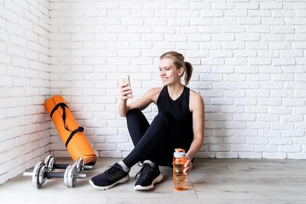 Młoda Uśmiechnięta Kobieta Fitness Robi Selfie Po Treningu, Siedząc Na Podłodze Wody Pitnej Premium Zdjęcia