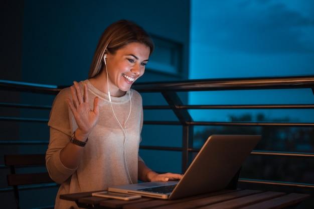 Młoda Uśmiechnięta Kobieta Ma Połączenie Wideo Używać Laptop, Przy Nocą. Premium Zdjęcia
