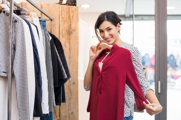 Młoda Uśmiechnięta Kobieta Próbuje Nowych Ubrań W Centrum Handlowym Premium Zdjęcia