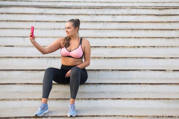 Młoda Uśmiechnięta Plus Size Kobieta W Sportowej Bluzce I Legginsach Siedzi Na Schodach, Szczęśliwie Robiąc Zdjęcie Na Telefon Komórkowy, Spędzając Czas Na świeżym Powietrzu Premium Zdjęcia