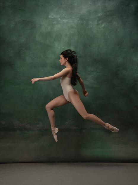 Młoda Wdzięczna Balerina Przetargu Na Ciemnozielonej Przestrzeni Studio Darmowe Zdjęcia