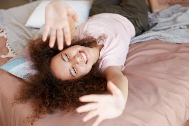 Młoda Wesoła Afroamerykanka Cieszy Się Słonecznym Dniem W Domu, Spędza Wolny Dzień I Odpoczywa W Domu, Leżąc Na łóżku I Szeroko Uśmiechając Się Z Zamkniętymi Oczami I Rękami Do Góry. Darmowe Zdjęcia