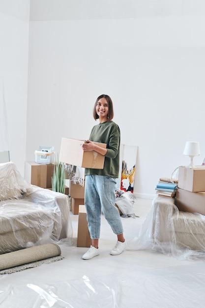 Młoda Wesoła Kobieta W Codziennym Noszeniu Pudełka Z Rzeczami, Poruszając Się Po Salonie Nowego Mieszkania Lub Domu Premium Zdjęcia