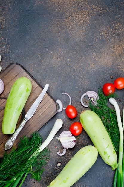 Młoda wiosenna cukinia, pomidory, zioła i przyprawy na czarnej powierzchni Premium Zdjęcia