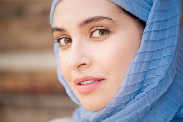 Młoda Wspaniała Muzułmańska Kobieta W Niebieskim Hidżabie Patrząc Prosto Podczas Pozowania Na Zewnątrz Premium Zdjęcia