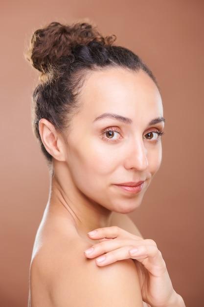 Młoda Wspaniała Spokojna Brunetka Z Ręką Na Gołym Ramieniu, Patrząc Na Ciebie Z Uśmiechem Premium Zdjęcia