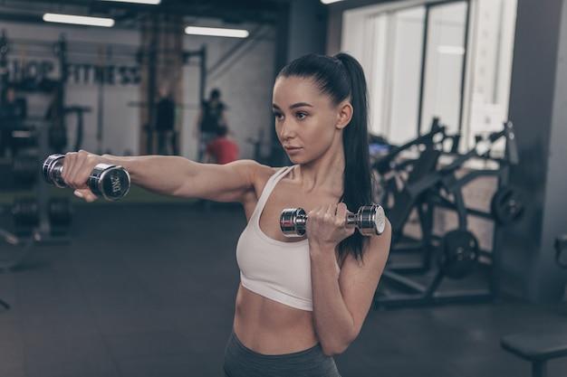 Młoda zdrowa kobieta cieszy się pracujący z dumbbells przy gym out. Premium Zdjęcia