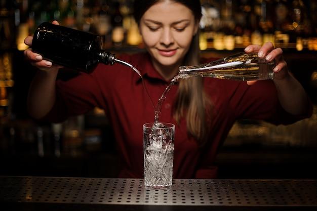 Młoda żeńska Barman Doniczkowy Dżin I Słodki Syrop W Szkło Premium Zdjęcia