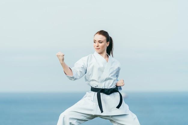 Młoda żeńska Karate Atleta Przygotowywa Atakować. Ma Na Sobie Czarny Pas I Białe Kimono Premium Zdjęcia