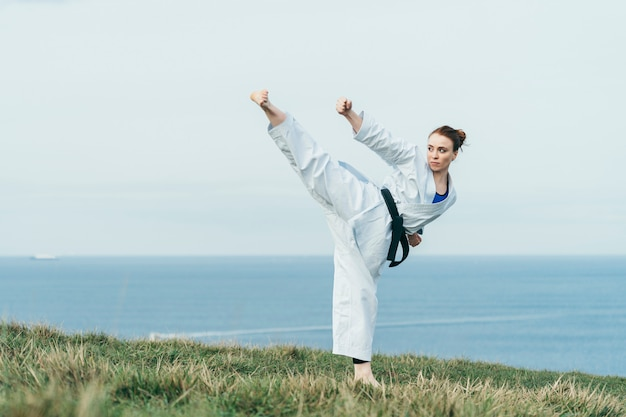 Młoda żeńska Rudzielec Karate Atleta Uderza Wysokiego Kopnięcie Premium Zdjęcia