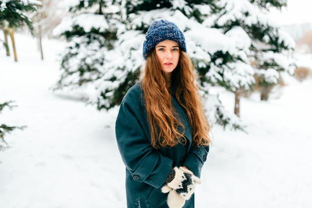 Młoda zmysłowa dziewczyna w zbyt dużym płaszczu z długimi pięknymi włosami stojącymi w winter park z zaśnieżonymi świerkami na tle. Premium Zdjęcia