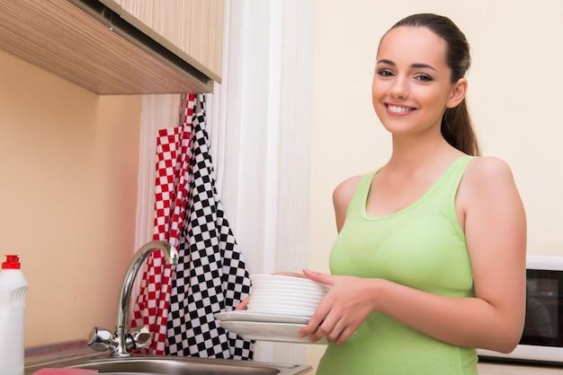 Młoda żona kobieta mycie naczyń w kuchni Premium Zdjęcia