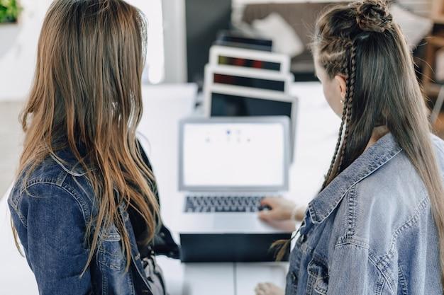Młode Atrakcyjne Dziewczyny W Sklepie Elektronicznym Używają Laptopa Na Wystawie. Koncepcja Kupowania Gadżetów. Darmowe Zdjęcia
