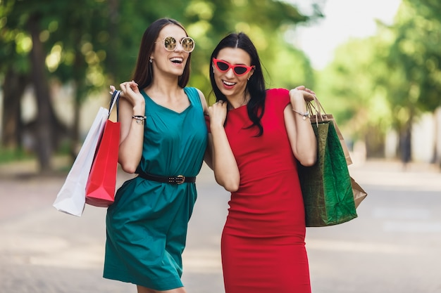 Młode atrakcyjne dziewczyny z torby na zakupy w mieście lato. piękne kobiety patrzeje kamerę i ono uśmiecha się w okularach przeciwsłonecznych. pozytywne emocje i koncepcja dzień zakupów. Premium Zdjęcia