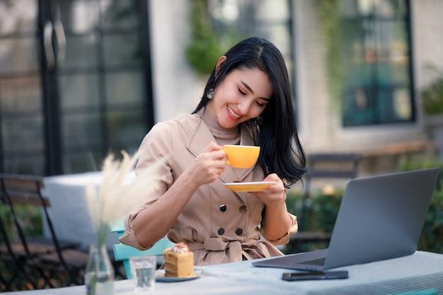 Młode Azjatyckie Kobiety Biznesu I Wolny Strzelec Siedzący Na Drewnianym Stole W Ogrodzie I Relaksujący Picie Kawy Premium Zdjęcia