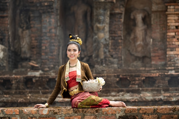 Młode azjatyckie kobiety w tradycyjnych strojach siedzą na starej ścianie i trzymają w ręku srebrny łuk ot lotosu. piękne dziewczyny w tradycyjnych strojach. tajska dziewczyna w retro tajskiej sukni. Premium Zdjęcia