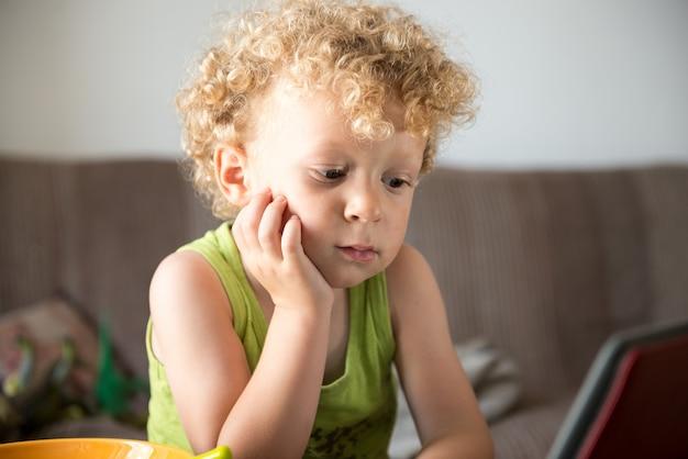 Młode blond dziecko wygląda na tablet Premium Zdjęcia