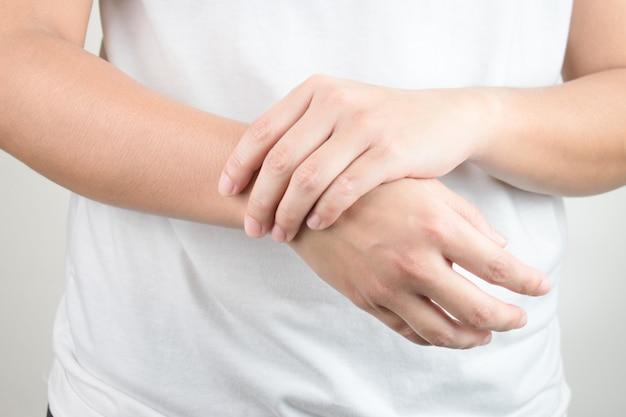 Młode dłonie trzymające drugą stronę nadgarstka. Premium Zdjęcia