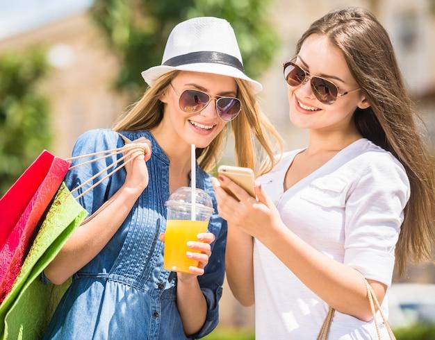 Młode dziewczyny patrzeje telefon i ono uśmiecha się z torba na zakupy. Premium Zdjęcia