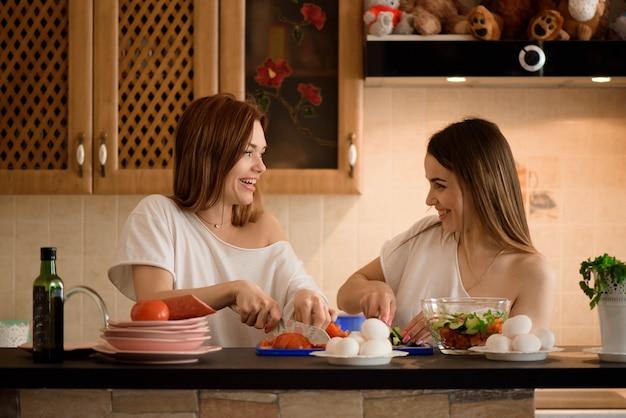 Młode Dziewczyny Siekają Warzywa Z Bliźniakiem W Rodzinnej Domowej Kuchni. Premium Zdjęcia