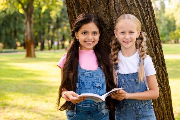 Młode dziewczyny trzyma książkę i patrzeje kamerę Darmowe Zdjęcia
