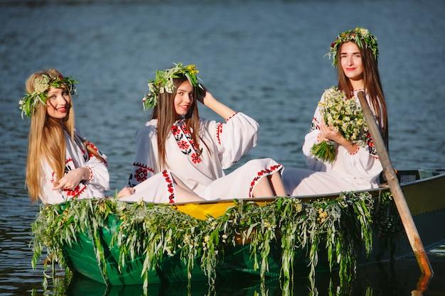 Młode dziewczyny w strojach ludowych pływają łodzią ozdobioną liśćmi i porostami. słowiańskie święto iwana kupały. Premium Zdjęcia