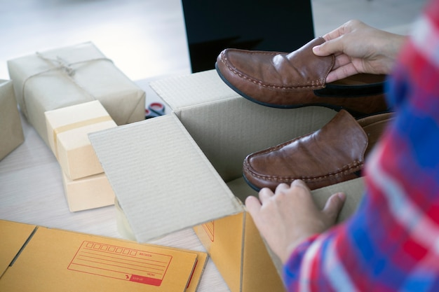 Młode kobiety biznesu przygotowują pudełka do dostarczania produktów kupującym online. Premium Zdjęcia