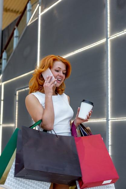 Młode Kobiety Rozmawia Przez Telefon Z Pakietami Zakupy W Nowoczesnym Centrum Handlowym. Koncepcja Zakupów. Koncepcja Czarny Piątek. Szczęśliwe Kobiety. Trzymanie Paczek. Premium Zdjęcia