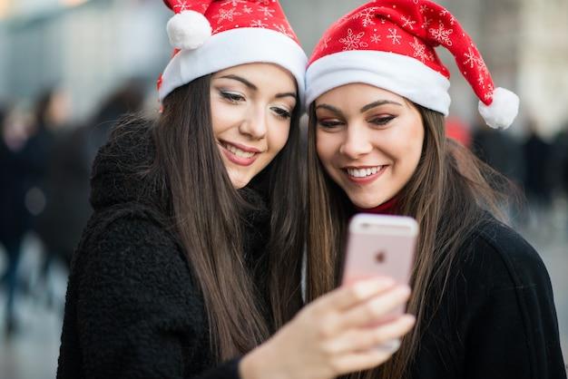 Młode Kobiety W Bożenarodzeniowym Kapeluszu Bierze Zdjęcie Wpólnie Premium Zdjęcia